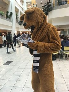 Nittany Lion looking at Lions Pantry pamphlet